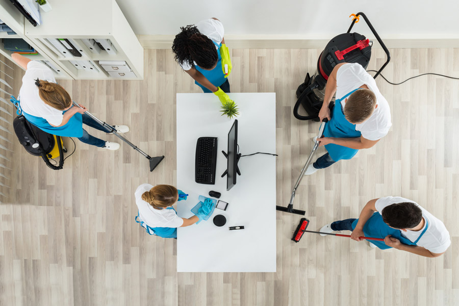 An overhead image of a commercial janitorial company cleaning an office space that has light colored wood flooring, a white desk with a black computer, and a white bookshelf in the rear left hand corner.
