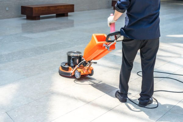 floor cleaning technician machine scrub cleaning a hard floor surface