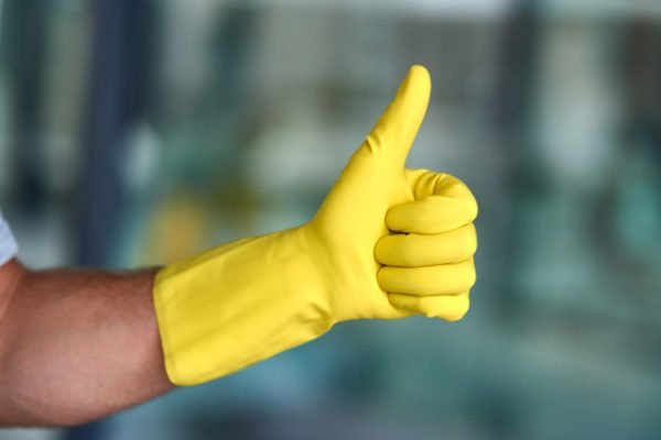 Thumbs-up from a professional janitor equipped with yellow cleaning gloves