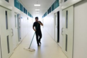 Janitorial Service - Cleaner Mopping Hallway