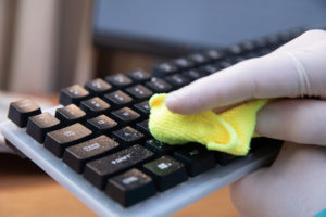 a professional disinfection company sanitizing a computer keyboard