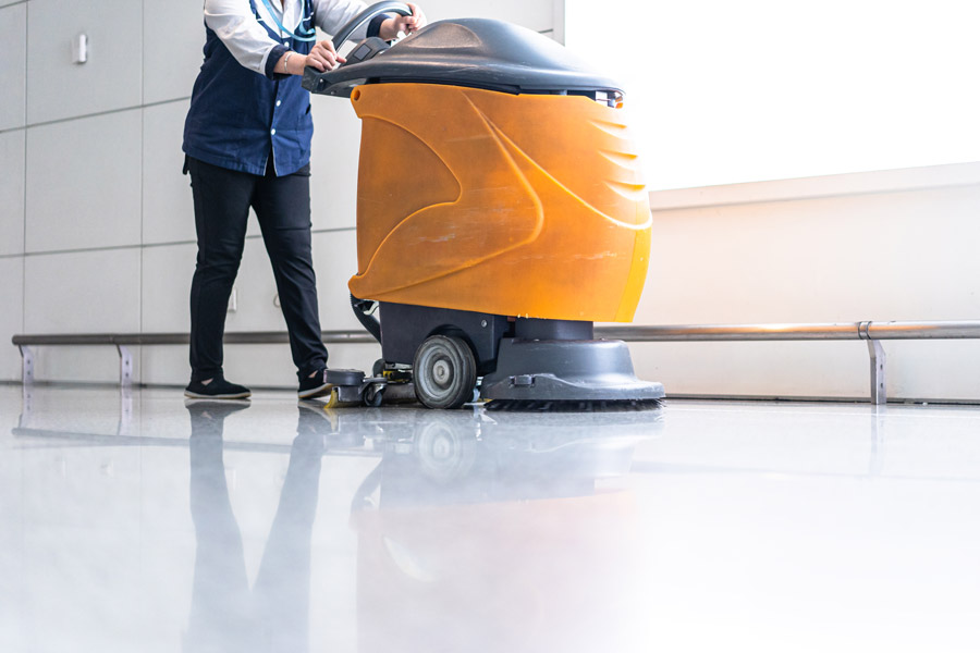 technician cleaning commercial floors with auto-scrub machine